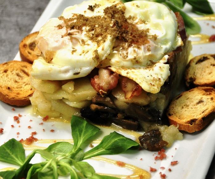 Huevos rotos camperos, con setas de temporada de La Fueva, trufa natural de Ribagorza y crujiente de panceta ibérica.