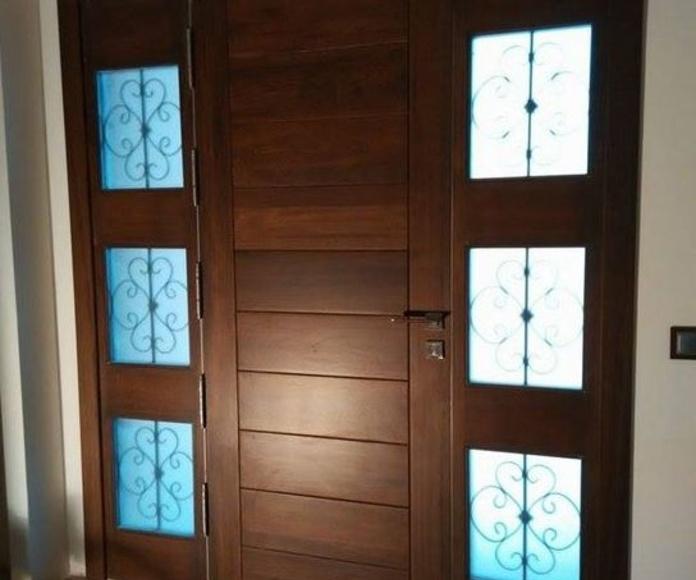 Puerta de entrada de madera maciza teñida en color nogal, con 2 fijos tipo vidriera.