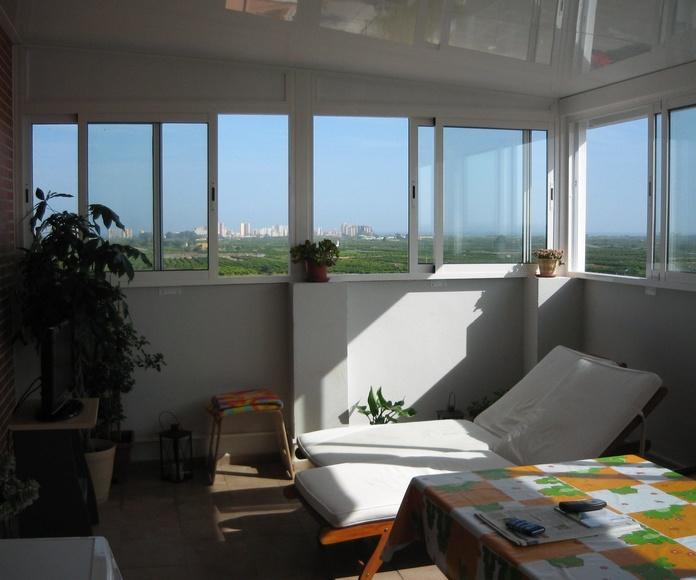 Cerramento de aluminio blanco con panel de 82mm. proteccion acustica exterior de caucho, ventanas correderas con celosia exterior.