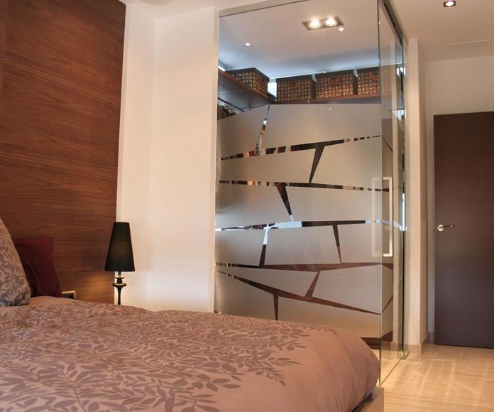 Armario con cerramiento de vidrio compuesto de un lateral fijo y otro con puerta corredera.