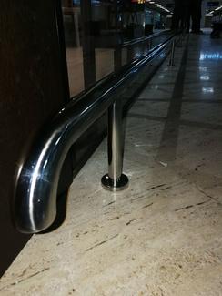 Paragolpes de acero inoxidable montado en escaparate de sala vip del aeropuerto.