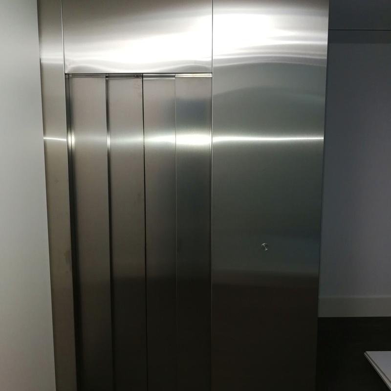 Forros de frente de ascensor fabricado con chapa de acero inoxidable satinado.