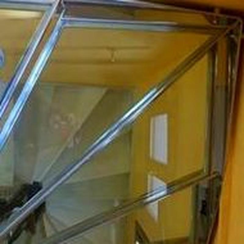 Escalera de acero inoxidable y vidrio con barandilla de acero inoxidable y pasamanos diseñada y fabricada a medida.