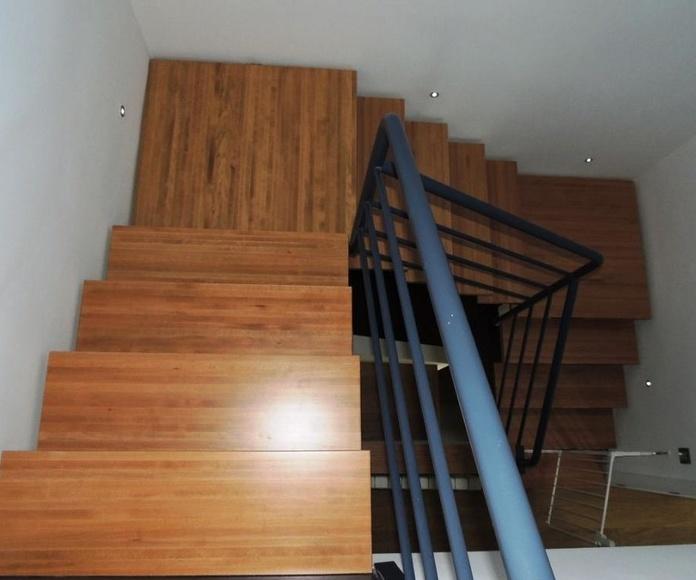 Peldaños de escalera en madera maciza teñidos igualando a la tarima.