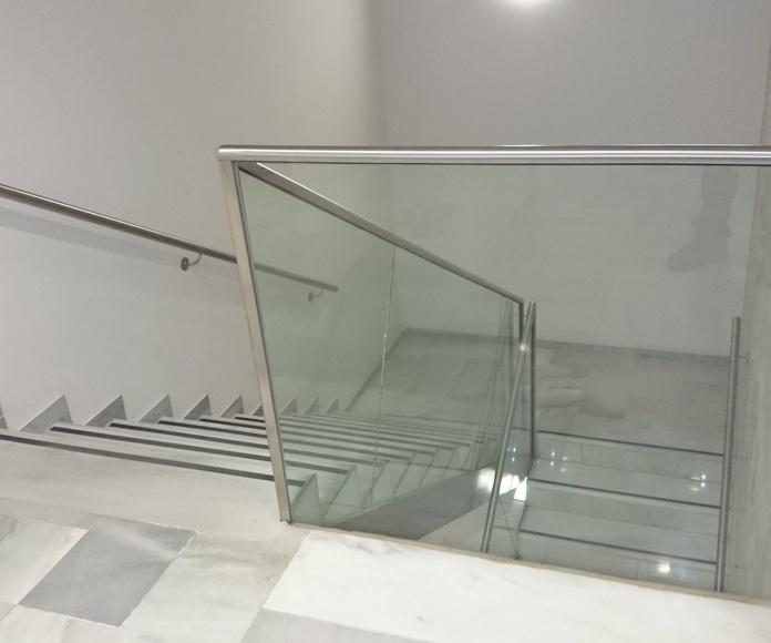 Barandilla de vidrio con pasamanos de acero inoxidable en edificio de administración pública.