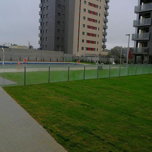 Barandilla de acero inoxidable y vidrio divisora de espacios en zona de piscina