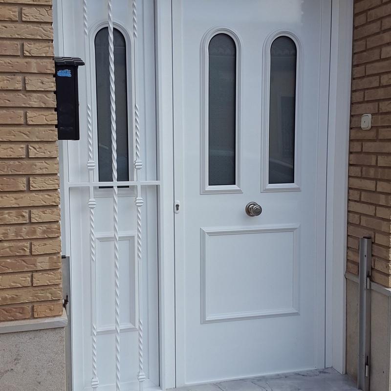 Puerta panelada con fijo lateral y reja de protección, en aluminio lacado blanco.