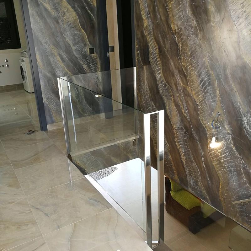 Barandilla de acero inoxidable y vidrio con pasamanos de acero inoxidable diseñada y fabricada a medida para vivienda particular