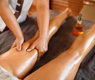 Masaje terapéutico de piernas con aceites esenciales