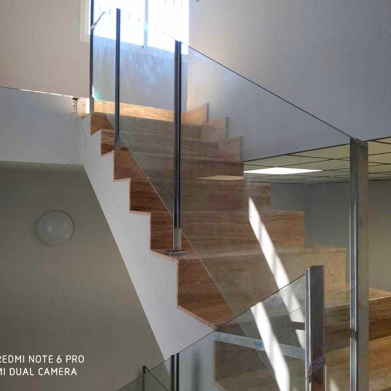 Barandilla de acero inoxidable para vidrio de seguridad sin pasamanos diseñada a medida y montada en oficinas de nave industrial.