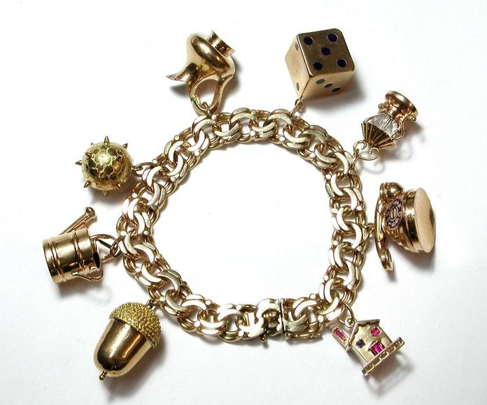 Pulsera barbada con diversos dijes realizados en oro con esmalte.: Catálogo de Antigua Joyeros