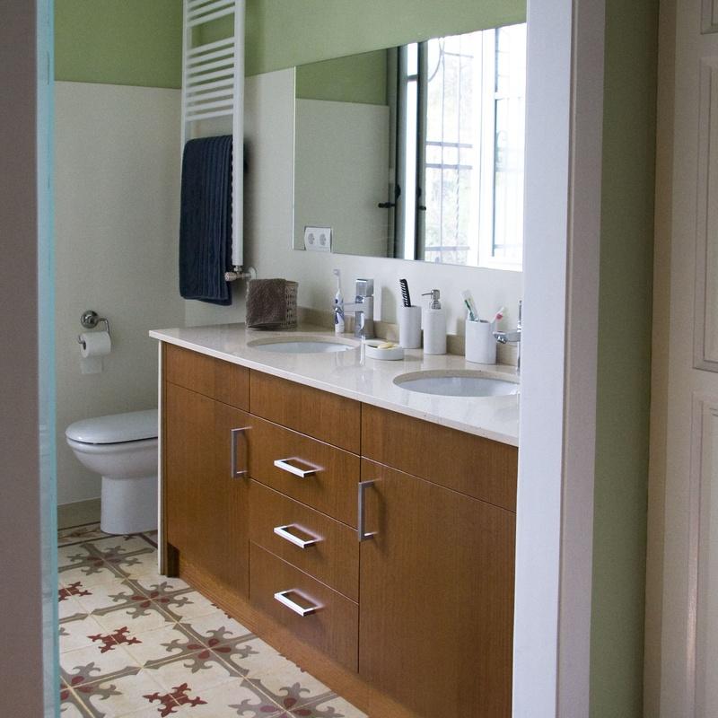 Baño con pavimento hidráulico recuperado; mueble a medida en roble tintado, la encimera de silestone.