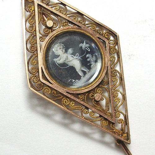Broche romboidal realizado en oro de 18k  con filibrana y tondo central con putti pintado en acuarela. Principios s. XIX. VENDIDO