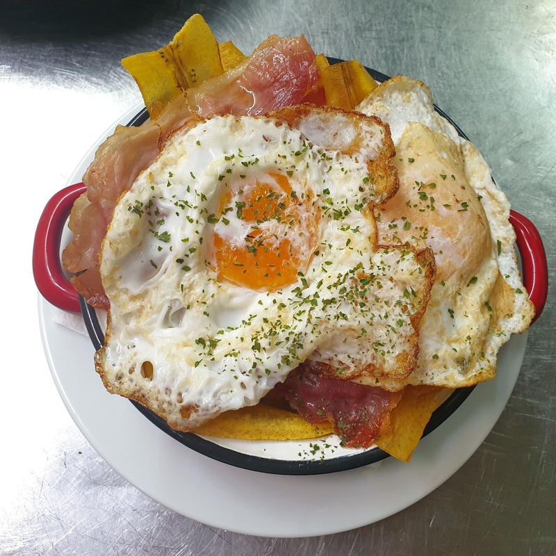 Sartén de huevos rotos, jamón y chips de plátano macho