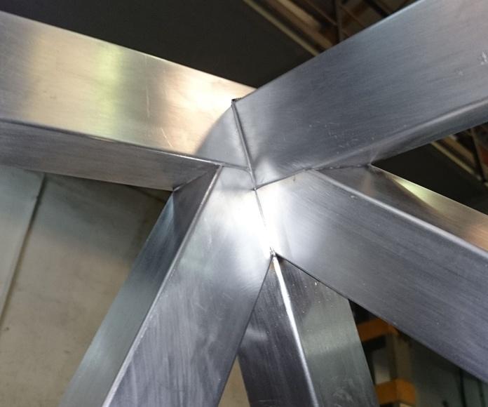Montera de diseño de acero inoxidable y vidrio montada como punto de luz para patio interior.