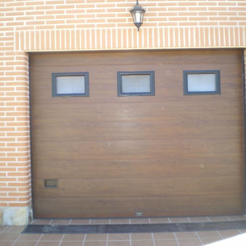 Puerta seccional color madera, con ventanas.