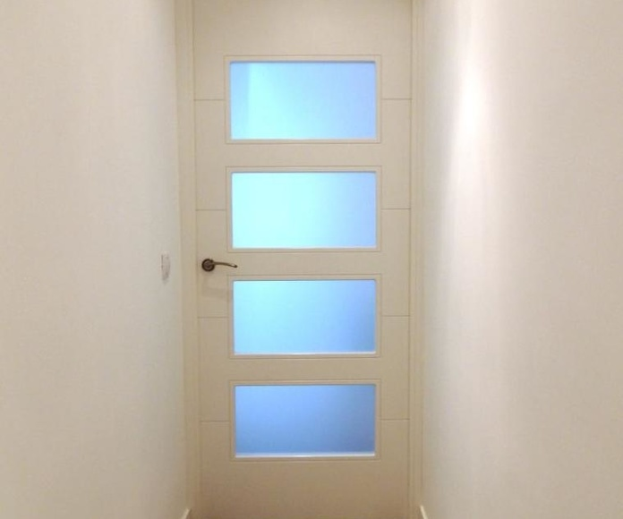 Puerta lacada en blanco y tarima laminada Quick Step Elite.