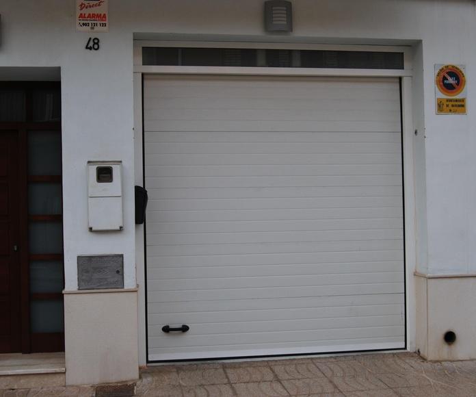 Puerta seccional de panel acanalado con fijo de vidrio superior.