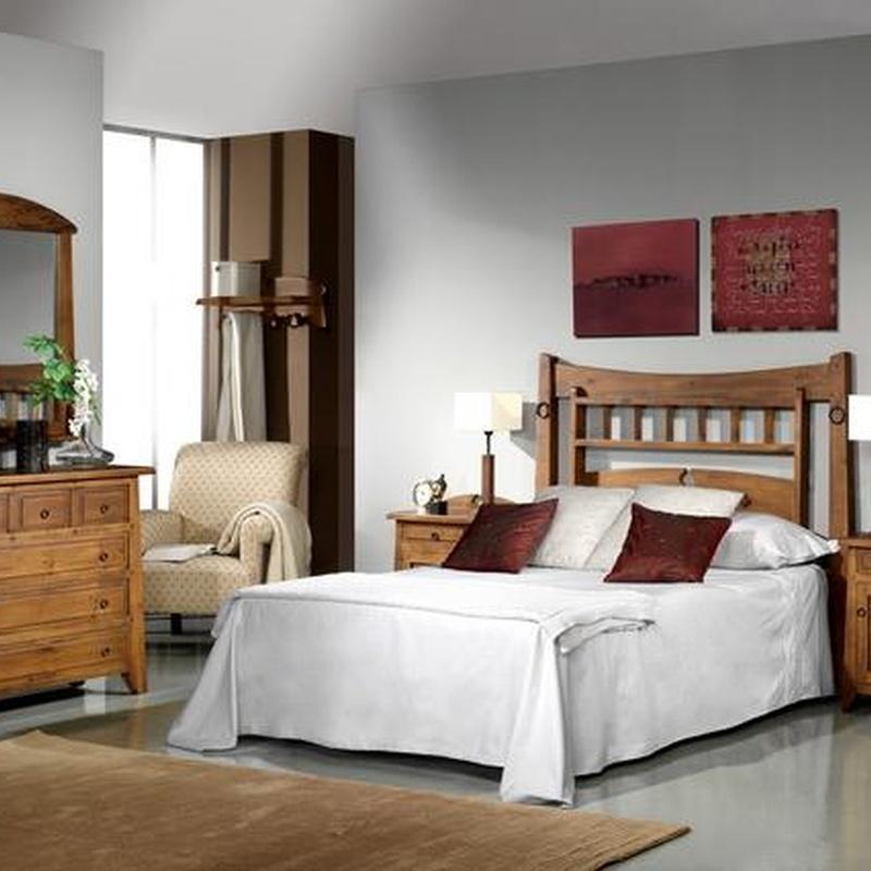Dormitorio rustico en pino macizo, con un cabecero con anillas.