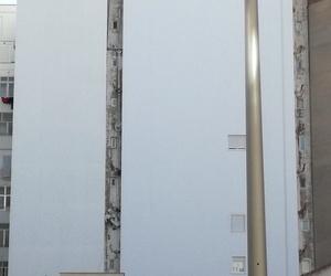 Retirada de bajantes con amianto con equipación especial (traje blanco, inferior izquierda), tras plan de trabajo y plan de seguridad aprobados