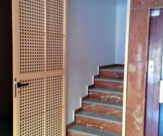 Puerta de hierro de 1 hoja abatible con paño fijo superior de chapa perforada con cerradura y muelle cierra-puertas