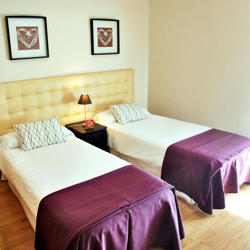Habitación con dos camas de 90cm, dotada de televisión y un práctico balcón