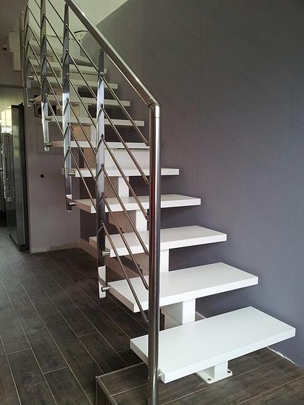 Escalera de madera con estructura central y baranda en inox