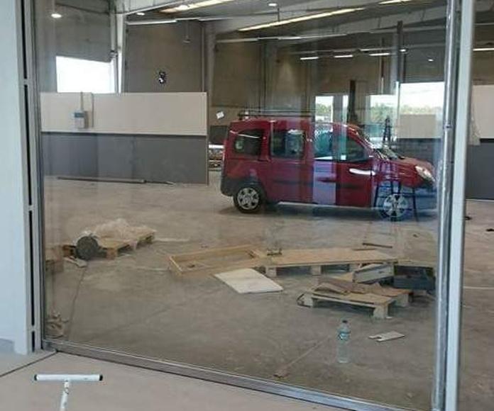 Puerta corredera de acero inoxidable y vidrio para acceso de vehículos en concesionario.