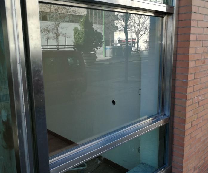 Ventana guillotina de acero inoxidable y vidrio montada en escaparate de local comercial.