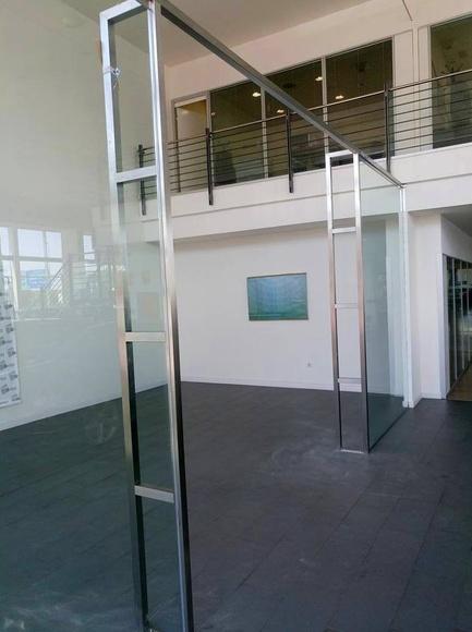 Pórtico de acero inoxidable para refuerzo de mampara de vidrio diseñada y montado en concesionario de coches