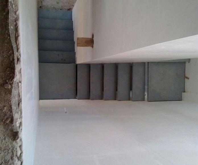Escalera de peldaños de hierro entre paredes, preparada para forrar