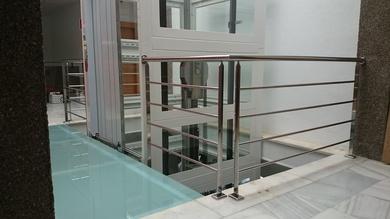 Barandilla de acero inoxidable en pasarela de acceso a ascensor montada para empresa privada.