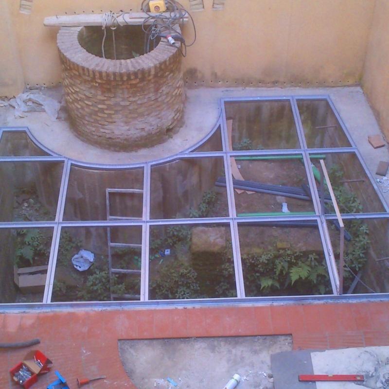 Suelo pisable de acero inoxidable con vidrios 10+10 montado en casa palacete, respetando zona de ruinas antiguas