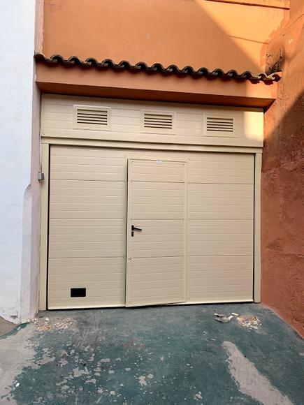 Puerta seccional con puerta peatonal rejillas.jpg