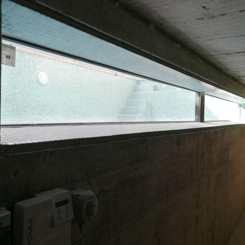 Ventana subacuática de acero inoxidable y vidrio para interior de piscina.