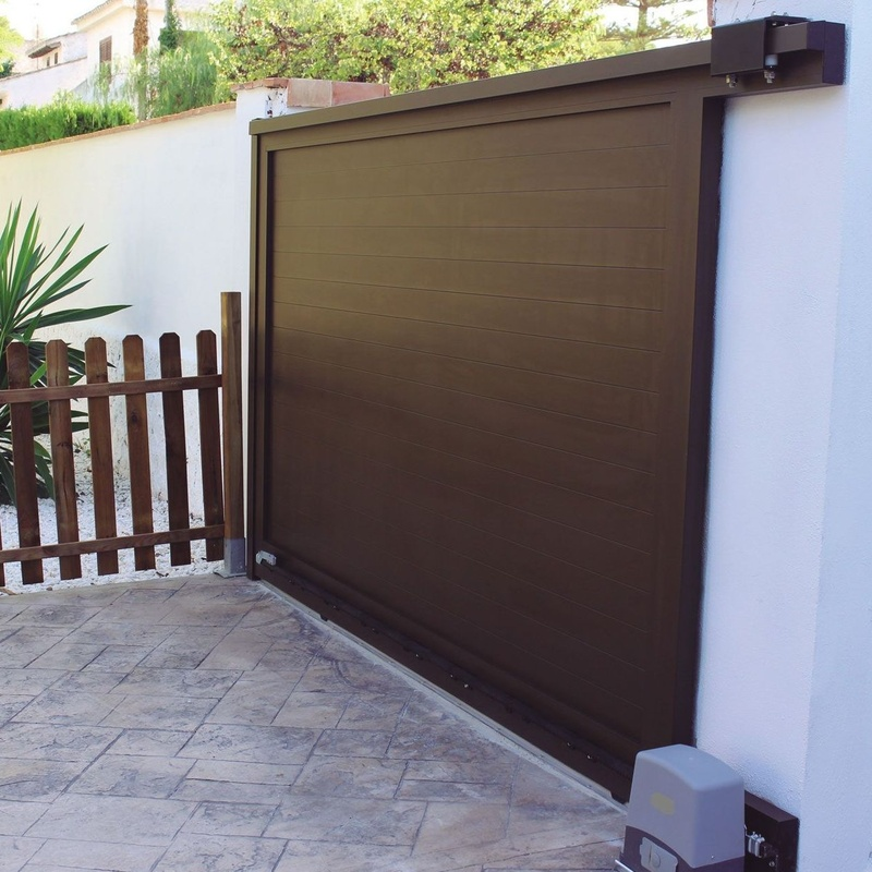 Puerta corredera automática de aluminio color madera oscura.