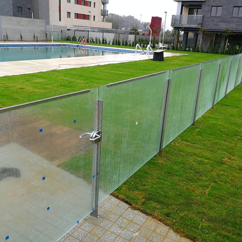 Barandilla de acero inoxidable y vidrio diseñada  para separar zonas comunes de comunidad de propietarios, protegiendo la zona de piscina de la zona de juegos. Contiene puerta de cristal templado para facilitar acceso de una zona común a otra.