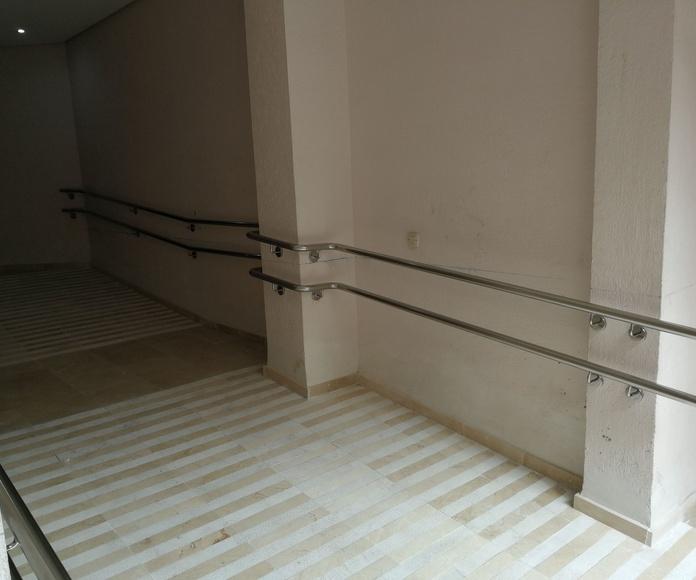 Pasamanos doble de acero inoxidable en rampa de minusválidos hecho a medida y adaptado a distintas zonas y vigas del edificio para comunidad de vecinos.