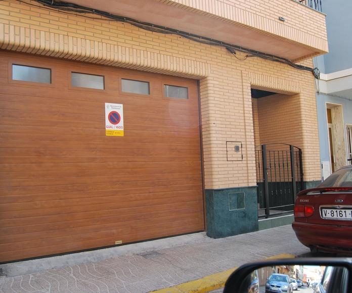 Puerta seccional de panel acanalado en color madera con fijos en el panel superior.