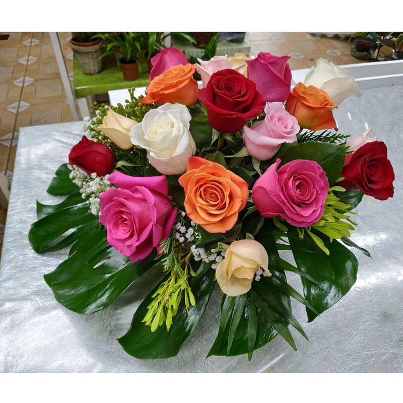 Arreglo de rosas variadas sobre hoja de mostera