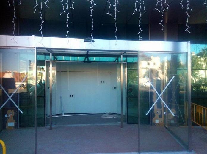 Cerramiento de puertas abatibles con fijos fabricada y montada en edificio de la junta de Andalucía