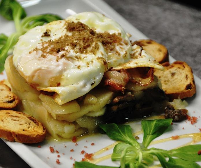 Huevos rotos camperos, con setas de temporada de La Fueva, trufa natural de Ribagorza y crujiente de panceta ahumada ibérica.