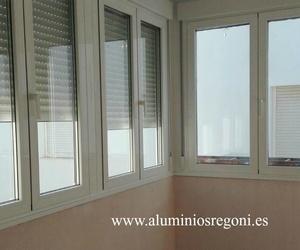 Cerramiento de aluminio lacado blanco con techo de panel sándwich de aluminio y carpintería de rotura de puente térmico con bisagras ocultas, cristal con control solar