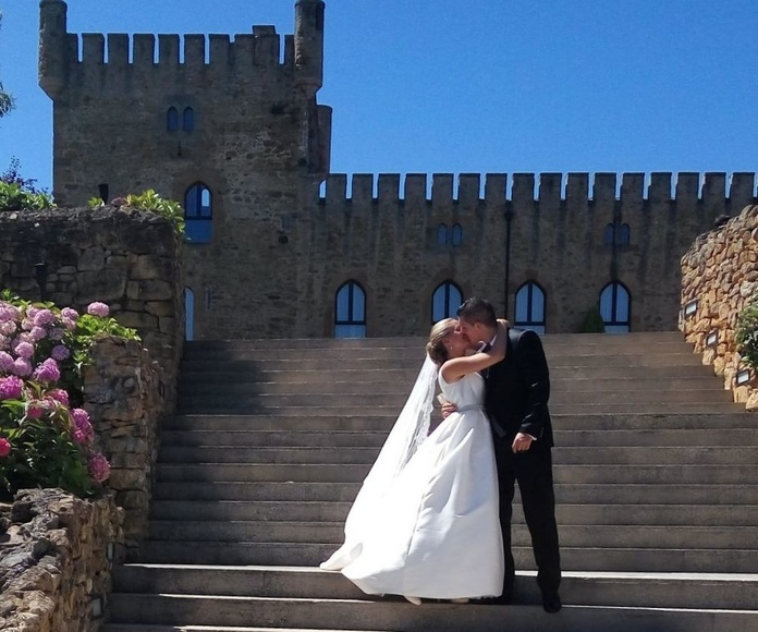 Foto de los novios el día de su boda frente al castillo en la escalinata