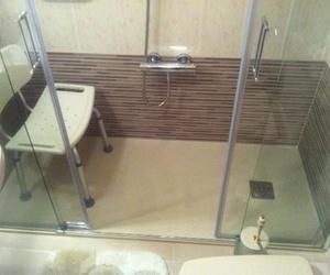 Plato de mármol técnico con azulejado. Asiento de ducha.