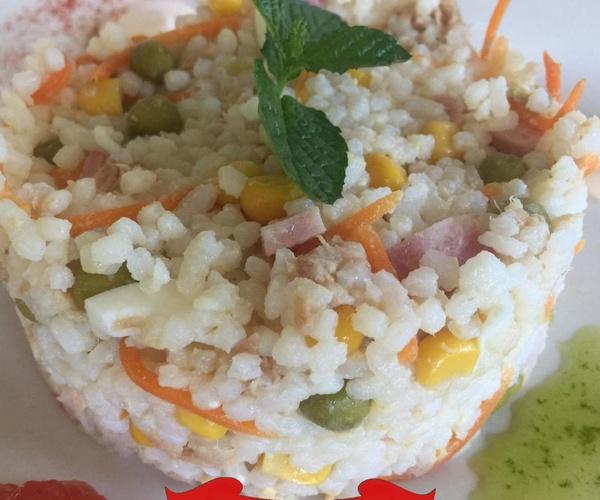 Ensalada de arroz con guarnición y salsa rosa de naranja
