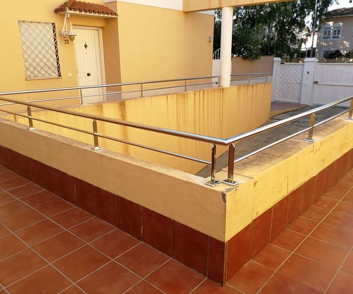 Barandilla de acero inoxidable diseñada y montada en acceso a garaje de comunidad de vecinos