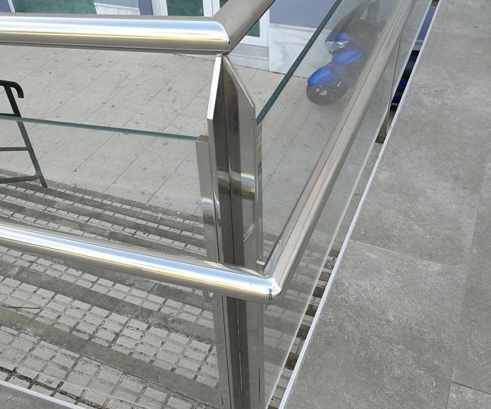 Barandilla de acero inoxidable y vidrio con pasamanos de acero inoxidable.