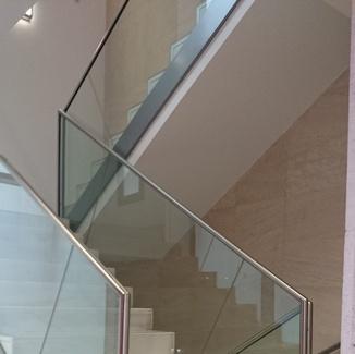 Barandilla de vidrio con pasamanos de acero inoxidable en edificio de la administración pública.