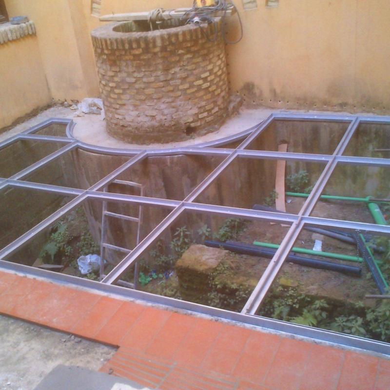 Suelo pisable de acero inoxidable con vidrios 10+10 montado en casa palacete, respetando zona de ruinas antiguas.